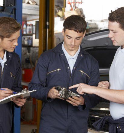 Mechanic Teaching Trainees In Garage Workshop